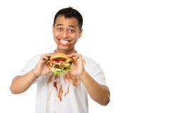 Lycklig ung man som äter en stor hamburgare Arkivfoto