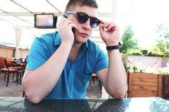 Lycklig ung man som tillfredsställs med bra mobil anslutning, i att ströva omkring, medan tala med vänner på smartphoneapparaten  royaltyfri bild