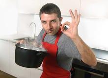Lycklig ung man som tillfredsställs med smak av hans matlagning som ger det ok tecknet Arkivfoto