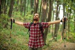 Lycklig ung man som tycker om ett perfekt fridsamt ögonblick under vandring till och med utsträckta skogarmar arkivfoton