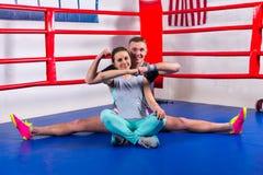 Lycklig ung manlig boxare som gör en splittring i sportswear nära hans flicka Royaltyfri Bild