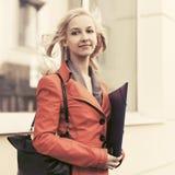 Lycklig ung modeaffärskvinna med mappmappen på kontorsbyggnad arkivfoton