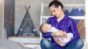 Lycklig ung moder som rymmer det älskvärda barnet och kysser hans handmedelskott
