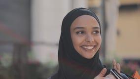 Lycklig ung muslim kvinna i hijab som går ner gatan med shoppingpåsar i hennes hand lager videofilmer