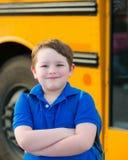 Lycklig ung pojke framme av skolbussen fotografering för bildbyråer