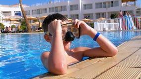 Lycklig ung pojke i att dyka maskeringen som kopplar av i p?l f?r bl?tt vatten p? hotellet av Egypten lager videofilmer