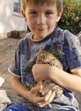 Lycklig ung pojke med den älsklings- kattungen Arkivbild