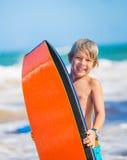 Lycklig ung pojke som har gyckel på stranden på semester, Arkivfoto