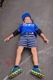 Lycklig ung pojke som kopplar av på hans skateboard Royaltyfri Bild