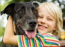 Lycklig ung pojke som kramar lovingly hans älsklings- hund Arkivfoto