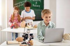 Lycklig ung pojke som ser bärbar datorskärmen royaltyfri foto