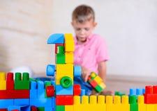 Lycklig ung pojke som spelar med hans byggnadskvarter Royaltyfria Bilder