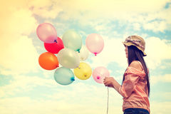 Lycklig ung röd hårkvinna som rymmer färgrika ballonger och flyger på molnhimmelbakgrund Royaltyfri Fotografi
