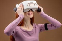 Lycklig ung r?dh?rig kvinna som anv?nder en virtuell verkligheth?rlurar med mikrofon royaltyfri foto
