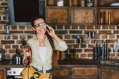 lycklig ung repairwoman i skyddande exponeringsglas med samtal för maktdrillborr royaltyfri foto
