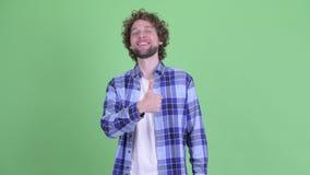 Lycklig ung skäggig hipsterman som ger upp tummar arkivfilmer