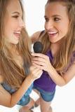 Lycklig ung skönhet som två tillsammans sjunger Arkivfoton