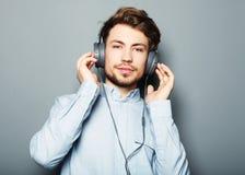 Lycklig ung stilfull man som justerar hans hörlurarannons som ler wh arkivfoto