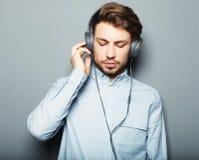 Lycklig ung stilfull man som justerar hans hörlurarannons som ler wh Royaltyfri Foto