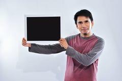 Lycklig ung stilig asiatisk man som rymmer och visar den tomma svart tavla eller br?det som ?r klara f?r din text fotografering för bildbyråer