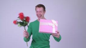 Lycklig ung stilig man med gåvaasken och rosor som är klara för valentin dag lager videofilmer
