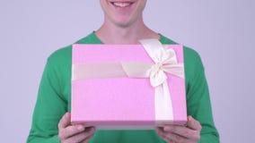 Lycklig ung stilig man med gåvaasken som är klar för valentin dag stock video