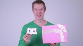 Lycklig ung stilig man med kalenderkvarteret och gåvaasken lager videofilmer