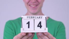 Lycklig ung stilig man med kalenderkvarteret som är klart för valentin dag stock video