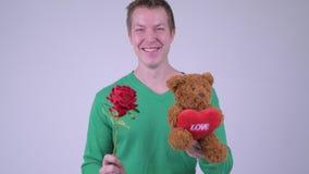 Lycklig ung stilig man med rosen och nallebjörnen som är klara för valentin dag arkivfilmer