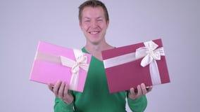 Lycklig ung stilig man med två gåvaaskar som är klara för valentin dag lager videofilmer