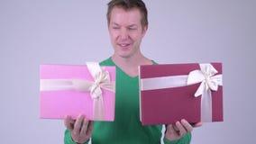 Lycklig ung stilig man med två gåvaaskar som är klara för valentin dag stock video