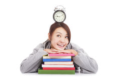 Lycklig ung student som ser klockan med böcker Royaltyfri Bild