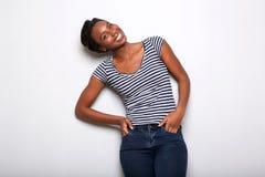 Lycklig ung svart kvinna som ler mot grå bakgrund royaltyfri bild