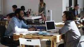 Lycklig ung svart manlig chef som talar till den attraktiva Caucasian affärskvinnan på den coworking kontorstabellen för moderikt lager videofilmer