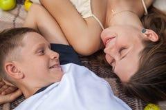 Lycklig ung syster och broder som poserar att ligga ner på plädet Royaltyfri Fotografi