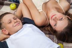 Lycklig ung syster och broder som poserar att ligga ner på plädet Arkivbild