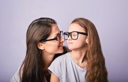 Lycklig ung tillfällig moder och leunge i modeexponeringsglas som kramar och ser sig på purpurfärgad bakgrund med den tomma kopia fotografering för bildbyråer