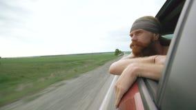 Lycklig ung turist- man som håller ögonen på i det kopplade av bilfönstret, medan resa stock video