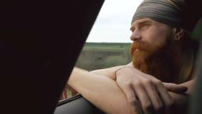 Lycklig ung turist- man som håller ögonen på i det kopplade av bilfönstret, medan resa arkivfilmer
