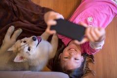 Lycklig ung unge som tar en selfie med hennes skrovliga hundvalp fotografering för bildbyråer