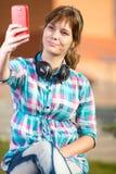 Lycklig ung wpman som tar bilder av henne till och med mobiltelefonen Selfie royaltyfri fotografi