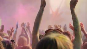 Lycklig ungdom som firar den Holi festivalen, ungt driftigt folk som dansar på partiet stock video