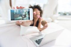 Lycklig ungdomlig mulattkvinna som underhåller med mobilen på stranden arkivbild