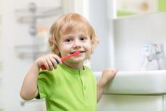Lycklig unge eller barn som borstar tänder i badrum tand- hygien royaltyfria bilder
