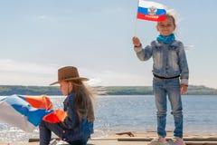Lycklig unge, gullig flicka för litet barn med den Ryssland flaggan mot en klar blå himmel royaltyfri fotografi