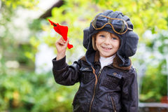 Lycklig unge i den pilot- hjälmen som spelar med leksakflygplanet Royaltyfria Bilder
