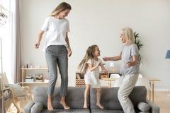 Lycklig unge, moder och farmor som har gyckel som hoppar på soffan arkivbild