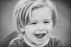 Lycklig unge som har gyckel Behandla som ett barn pojken med leende för blont hår på den utomhus- gulliga framsidan Arkivfoton