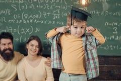 Lycklig unge som har gyckel Föräldrar som lyssnar deras son, svart tavla på bakgrund Pojke som framlägger hans kunskap till mamma Fotografering för Bildbyråer