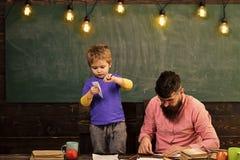 Lycklig unge som har gyckel Familjfritidsaktivitet Fader och gulliga nivåer för sondanandepapper Framkallande ungekreativitet Arkivfoto